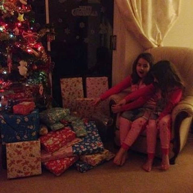 KayCee and Ella next to a pile of Christmas presents