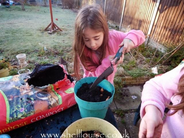 Ella adding more compost to the pot