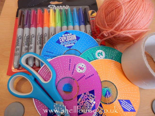 You will need: CDs, sharpies, thread, double sided tape and scissors