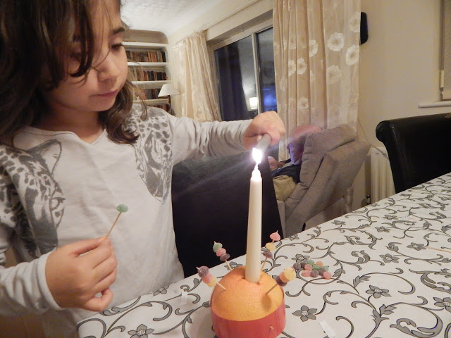 Ella lighting her Christingle