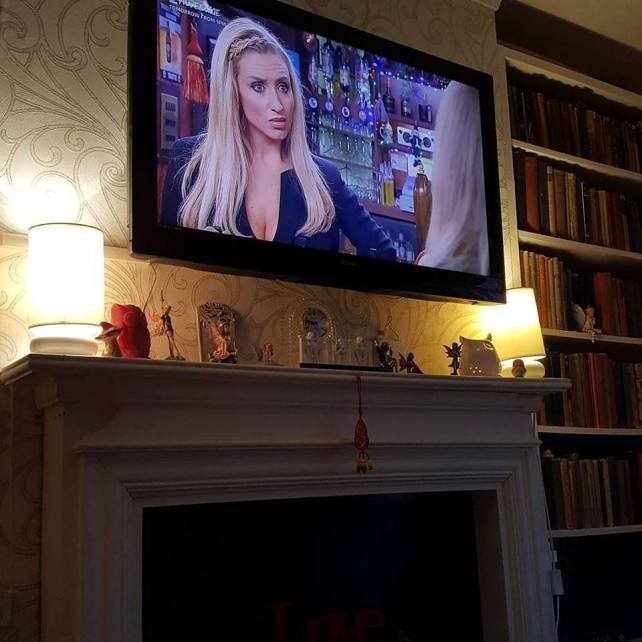 Corrie on the tv above the mantelpiece