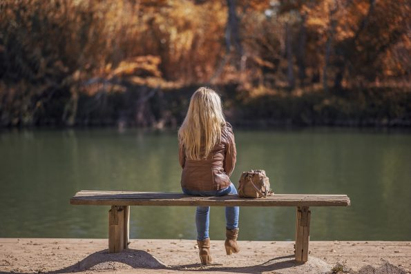 girl sitting by a lake wearing ankle boots