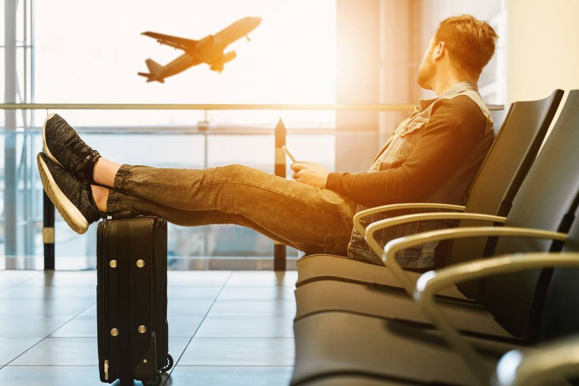 man at airport with his feet on oh his luggage - holiday purchases