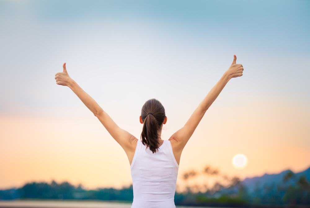 Combating negative thoughts - a lady is photographed from the back, she's holding up her arms and has her thumbs up for victory
