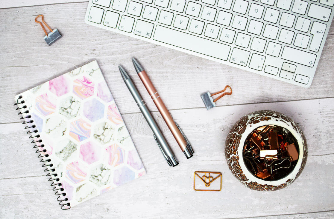 keeping blog readers engaged - keyboard, 2 pens, notebook, paperclips on white wooden background -