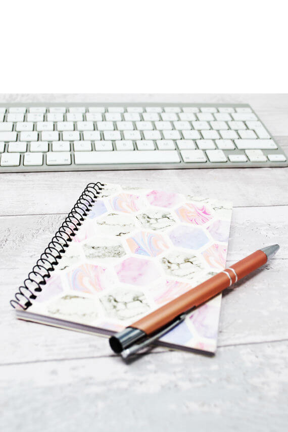blog flatlay - white keyboard, floral notebook and rose gold pen
