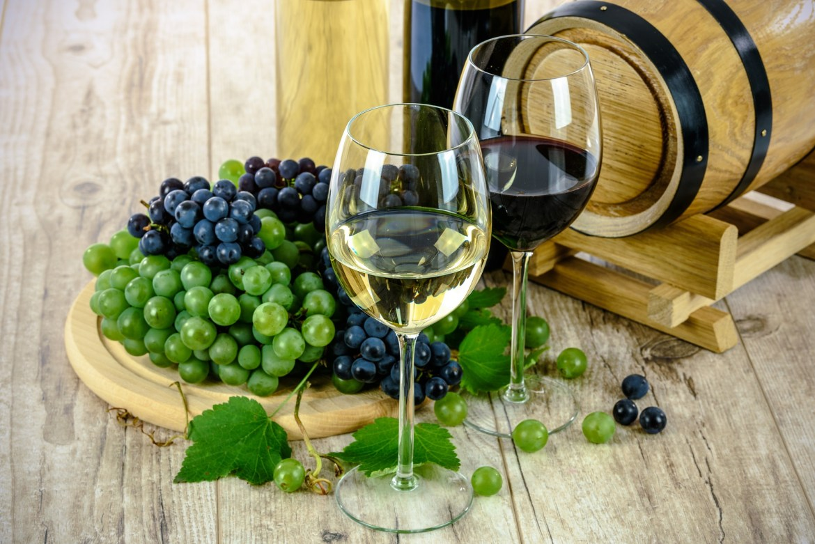 2 bottles of wine, a glass of white wine, a glass of red wine and grapes on a table - how to store fine wine