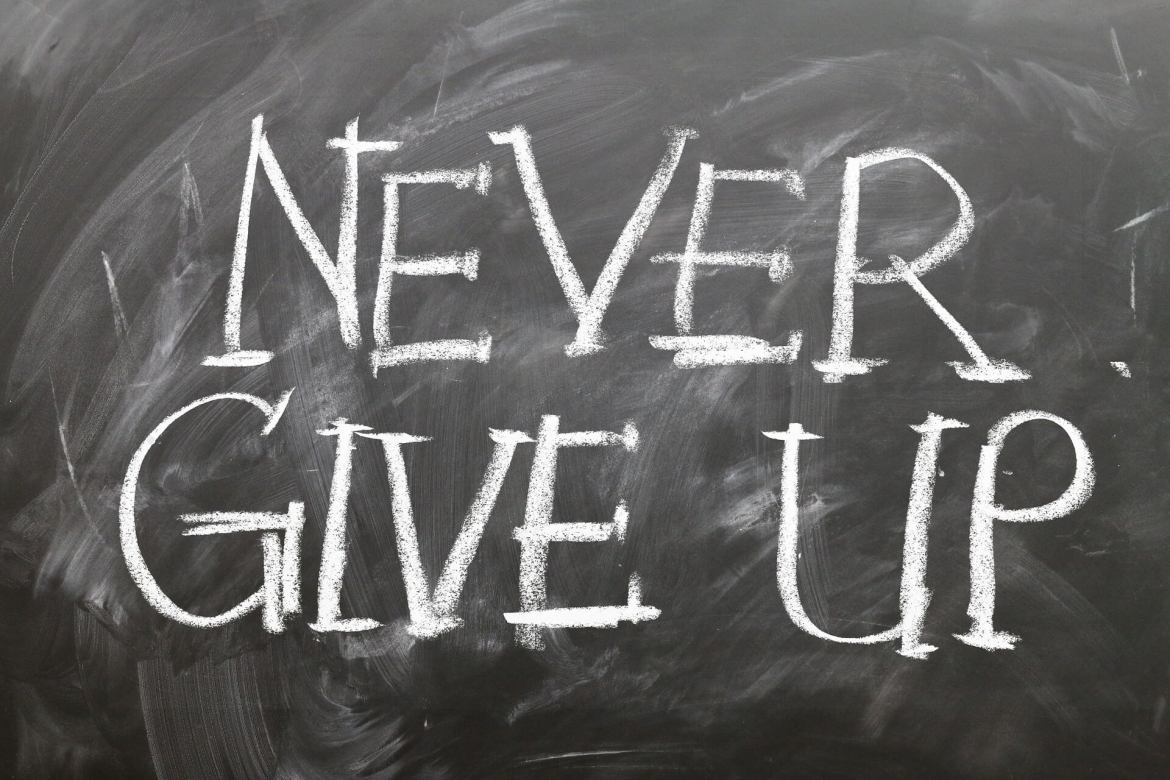 Encouraging hard work - Blackboard with Never give Up written on it in white chalk