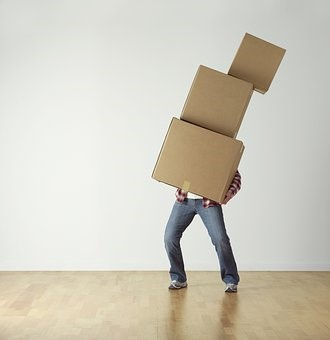 man moving a pile of boxes