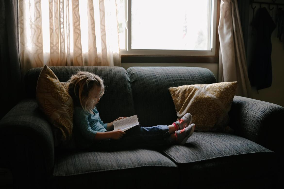 little girl on a sofa, reading a book