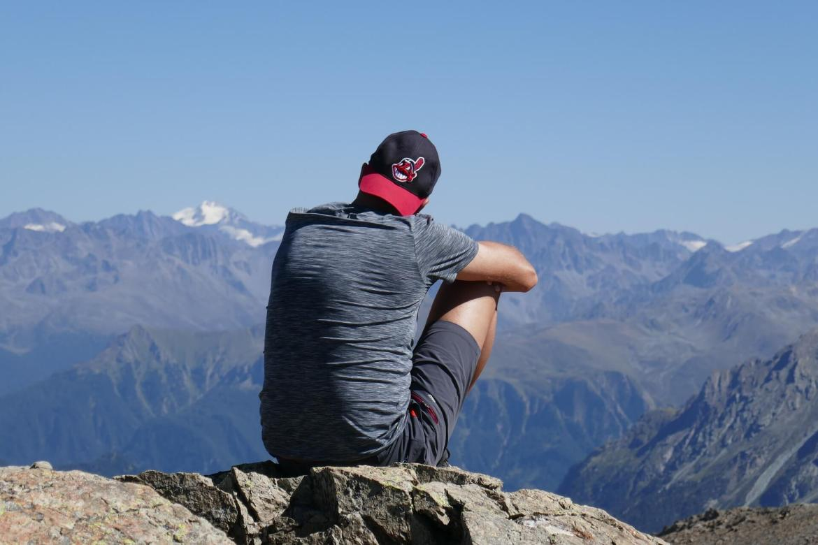 man sitting on a mountain - improve your finances and reach your goals