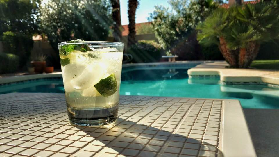 a drink at the side of a swimming pool - solar pool heaters