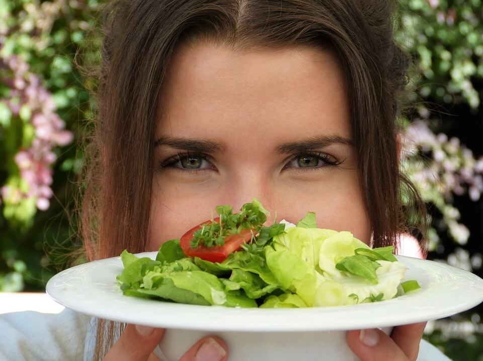 girl holding a plate of salad - body transformation