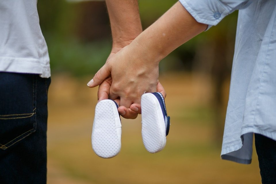 couple holding hands and carrying baby shoes -  egg donation IVF