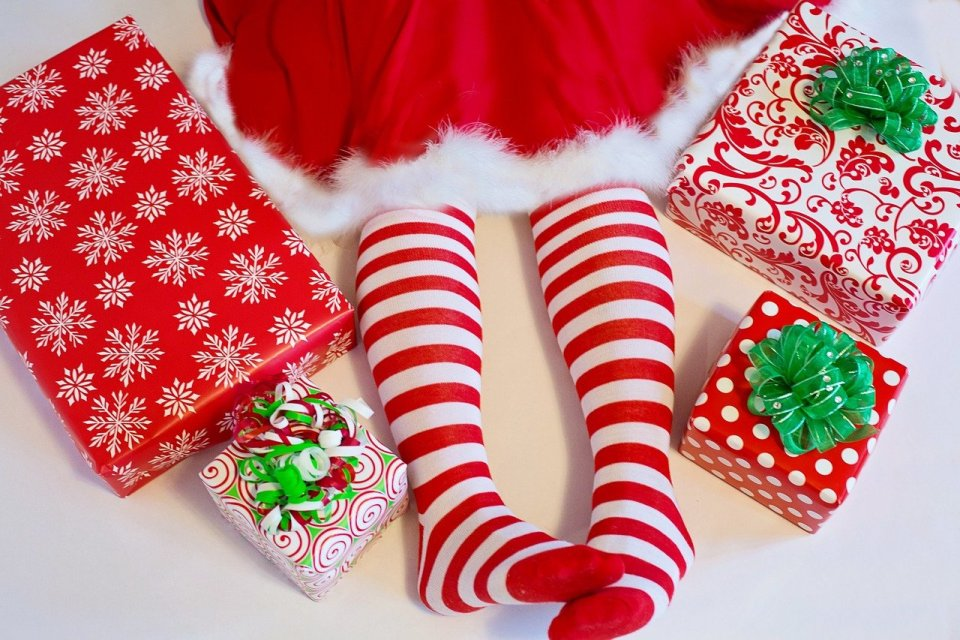 Girl wearing Mrs Claus skirt with red and white striped tights, surroundd by Christmas presents