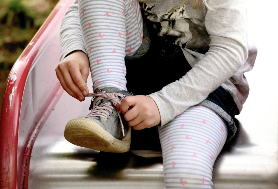 child tying the laces on her shoes