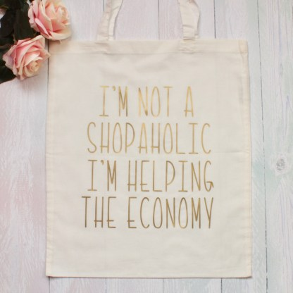 I'm not a shopaholic I'm helping the economy gold reusable tote bag