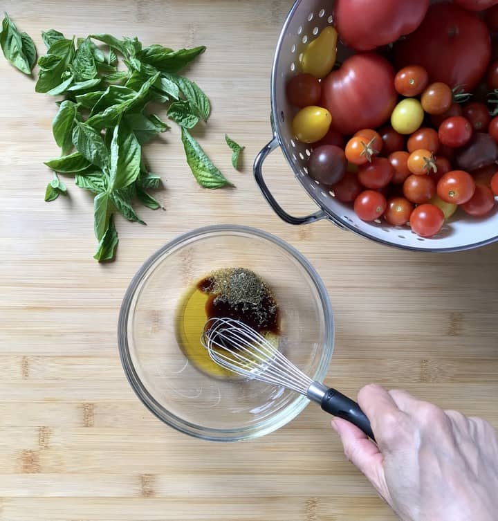 Ingredients for the tomato bruschetta marinade are being whisked together.