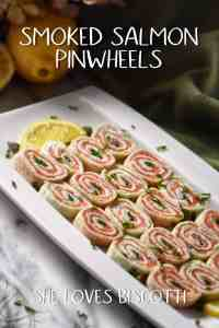 A white serving dish is filled with slices of smoked salmon pinwheels.