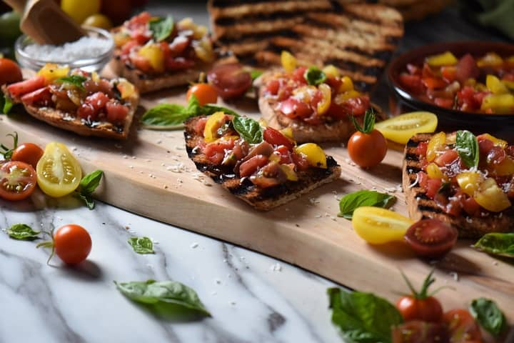 tomato topped bruschetta surrounded by cherry tomatoes and basil.