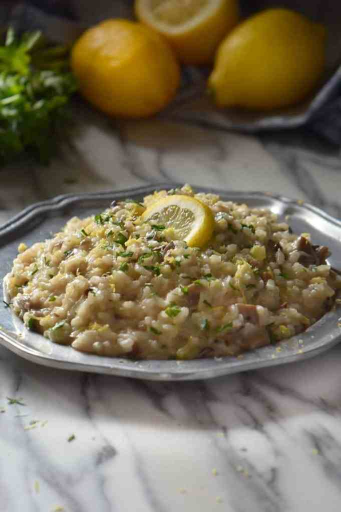 A plate of creamy mushroom risotto, topped with parsley. In the background, lemons and fresh Italian parsley can be seen.