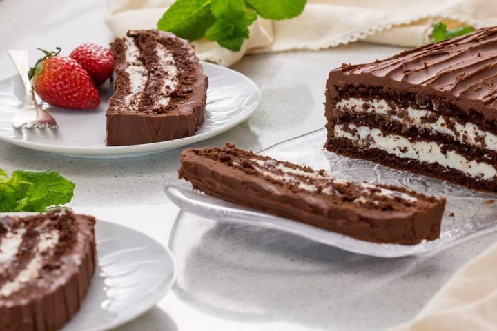 Slices of chocolate cream cake can be seen on white plates, served with strawberries.