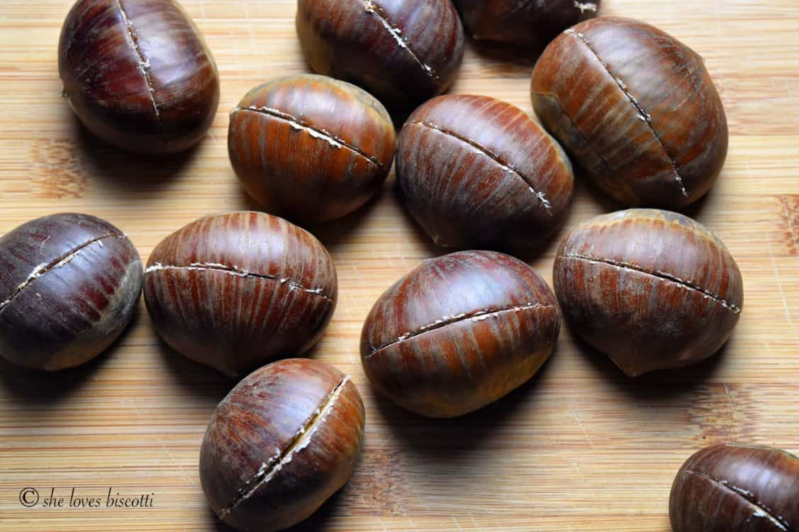A few chestnuts with a clear vertical incision through the outer skin.