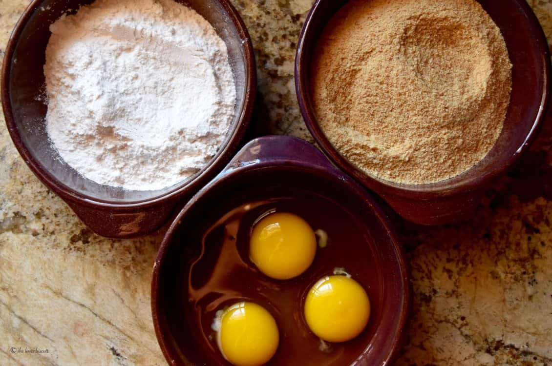 Flour, breadcrumbs and eggs are shown in three shallow bowls to dip the croquettes.