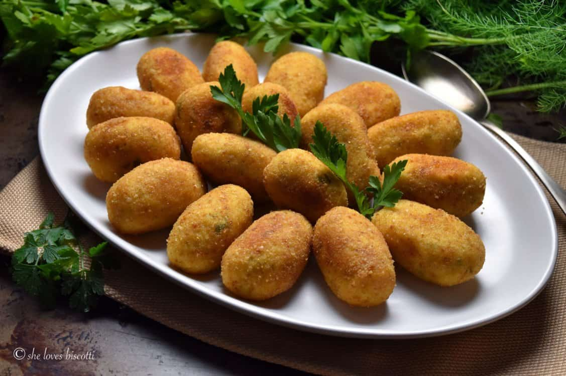 White serving platter with potato croquettes.