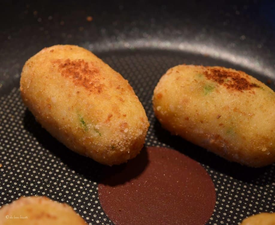 Potato croquettes being pan fried.