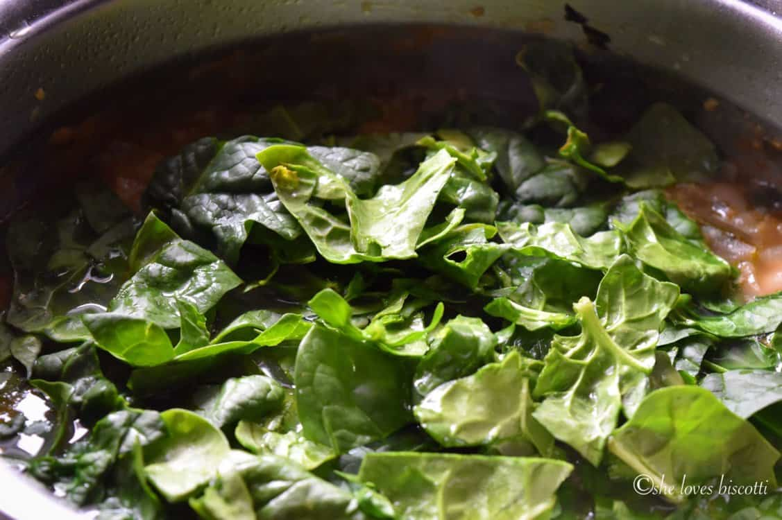 Spinach being added to the soup.