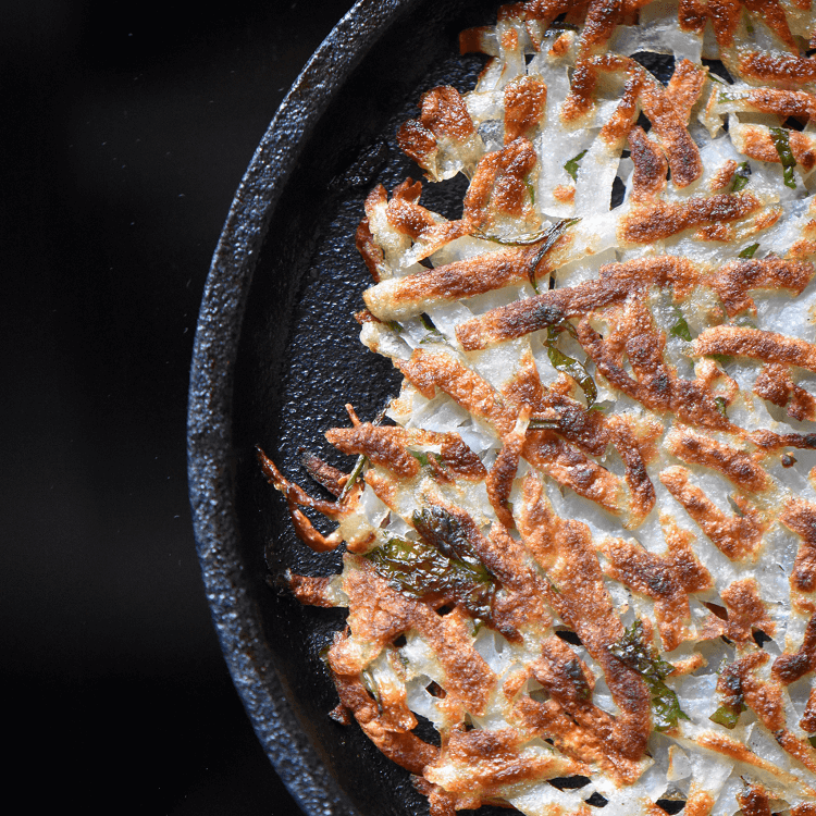 Crispy hash browns in a cast iron pan.