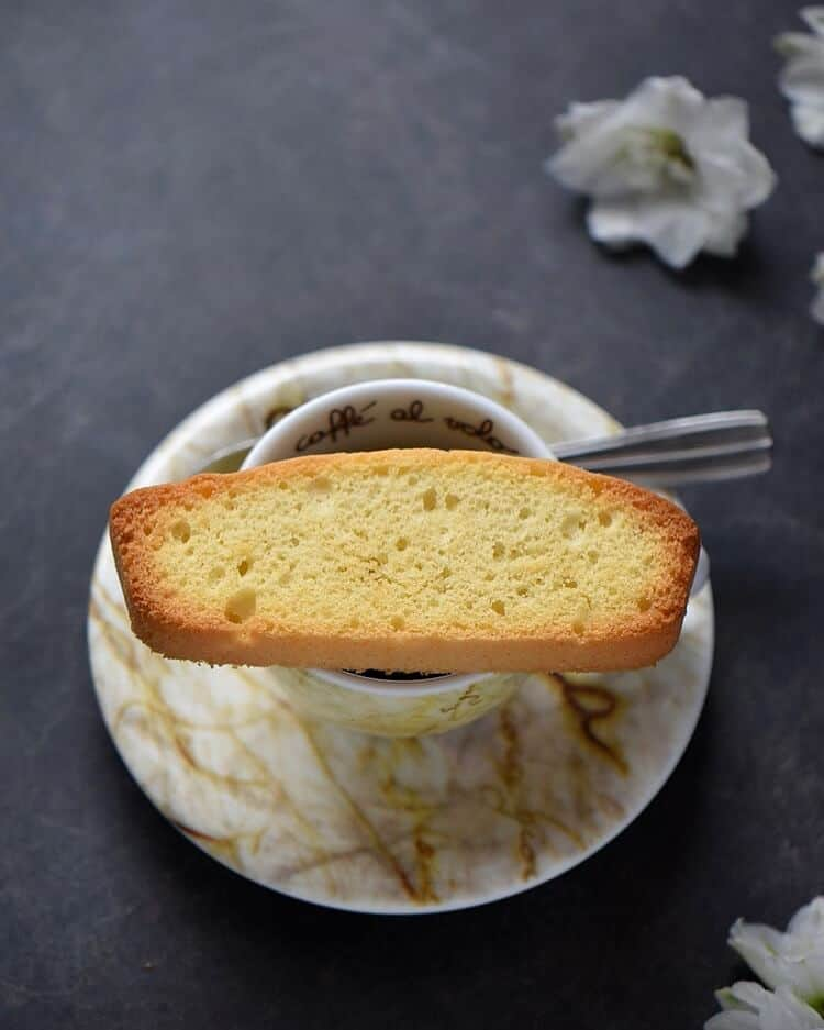 An overhead close up shot of a single Italian anise biscotti on an espresso cup.