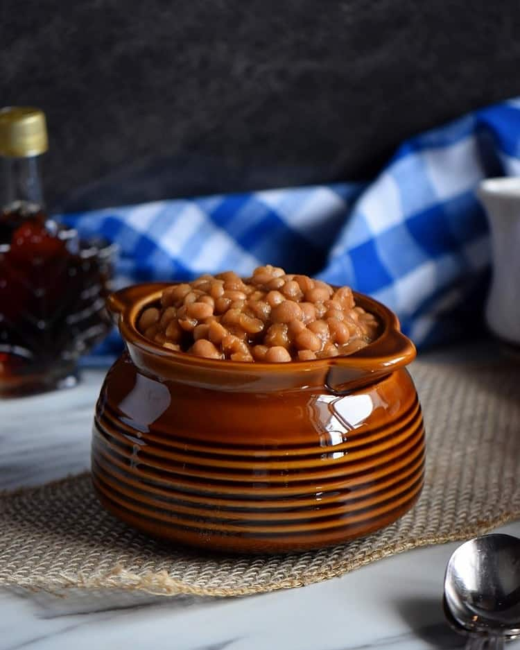 Homemade baked beans in a brown ceramic pot.