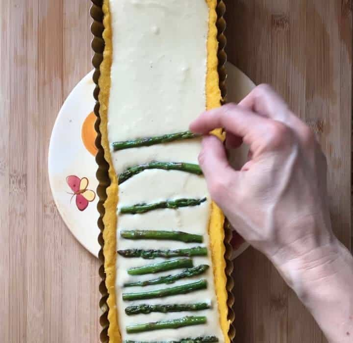 Sauted asparagus being place one by one on the ricotta filling.