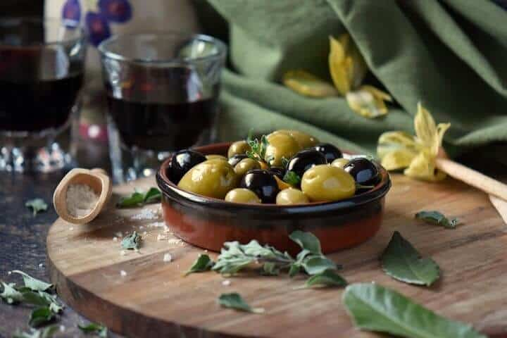 Marinated olives with a glass of wine in the background, surrounded by a few fresh oregano leaves.