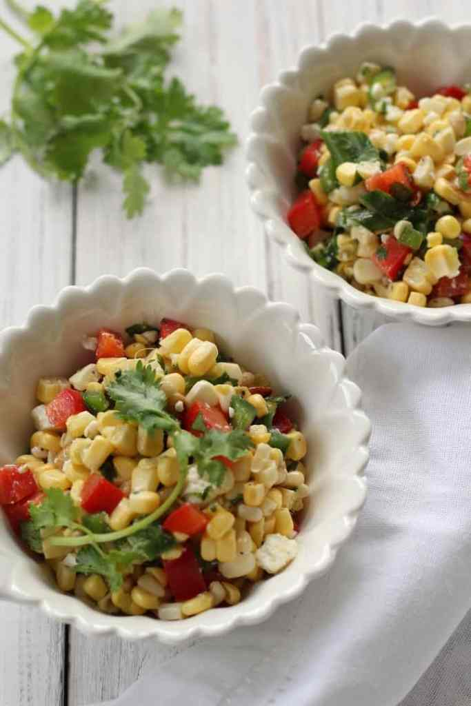 An overhead shot of two bowls of sweet corn salad.
