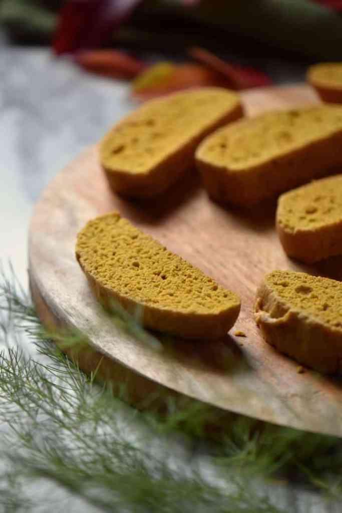 Sliced pumpkin biscotti on a wooden board.