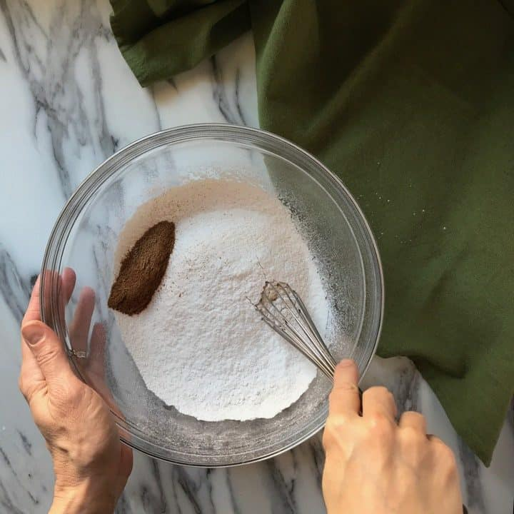 The dry ingredients to make pumpkin biscotti are in the process of being whisked together. These include all purpose and whole wheat flour, baking powder, and pumpkin spice.