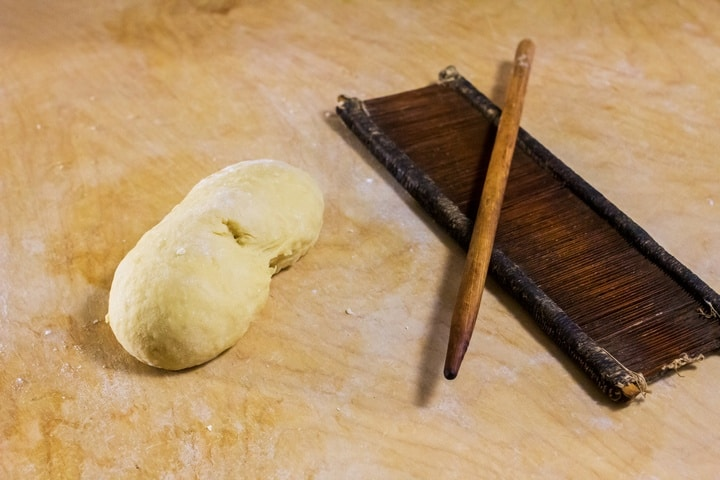 """A ball of dough and an original board and rod, called """"petene"""" and """"fuso"""" to make caragnoli."""