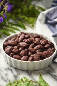 Dark chocolate covered almonds in a white ceramic dish.