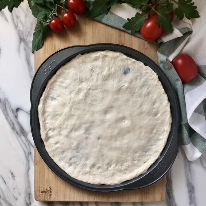 Pizza dough stretched out in a pan.