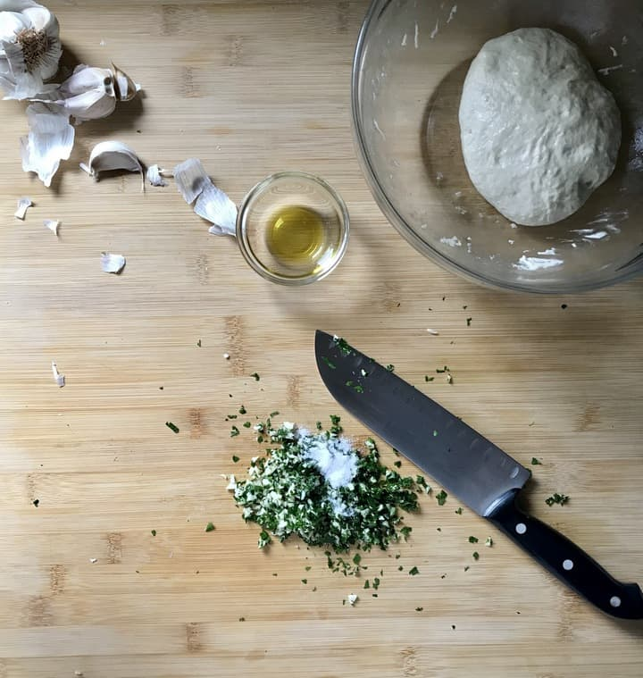 Chopped garlic and parsley are combined with the salt on a wooden board.
