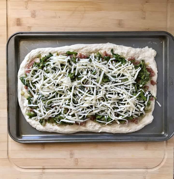 Broccoli rabe and mozzarella spread over pizza dough to make sausage pinwheels.