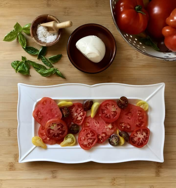 A variety of sliced heirloom tomatoes placed in a white serving dish.