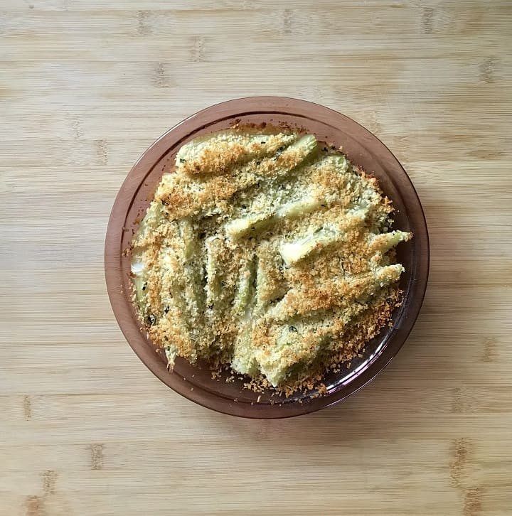 A round casserole dish of cooked fennel on a wooden board.