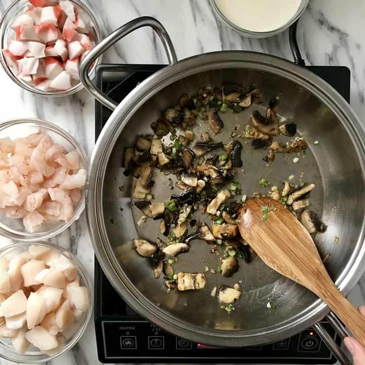 Small bowls of shrimp, scallops and crab about to be sauteed with mushrooms that ate already in a large pan.
