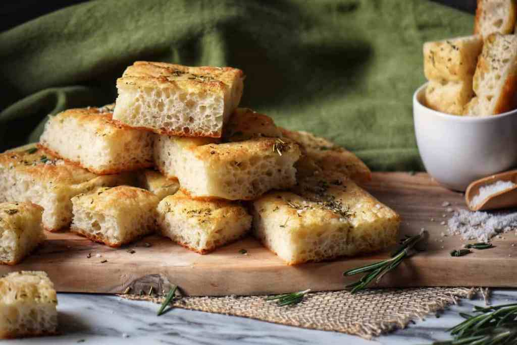 Italian focaccia on a wooden board surrounded by fresh rosemary.