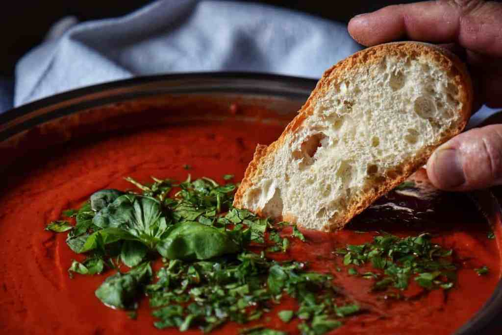A piece of Italian bread being dunked in tomato sauce.
