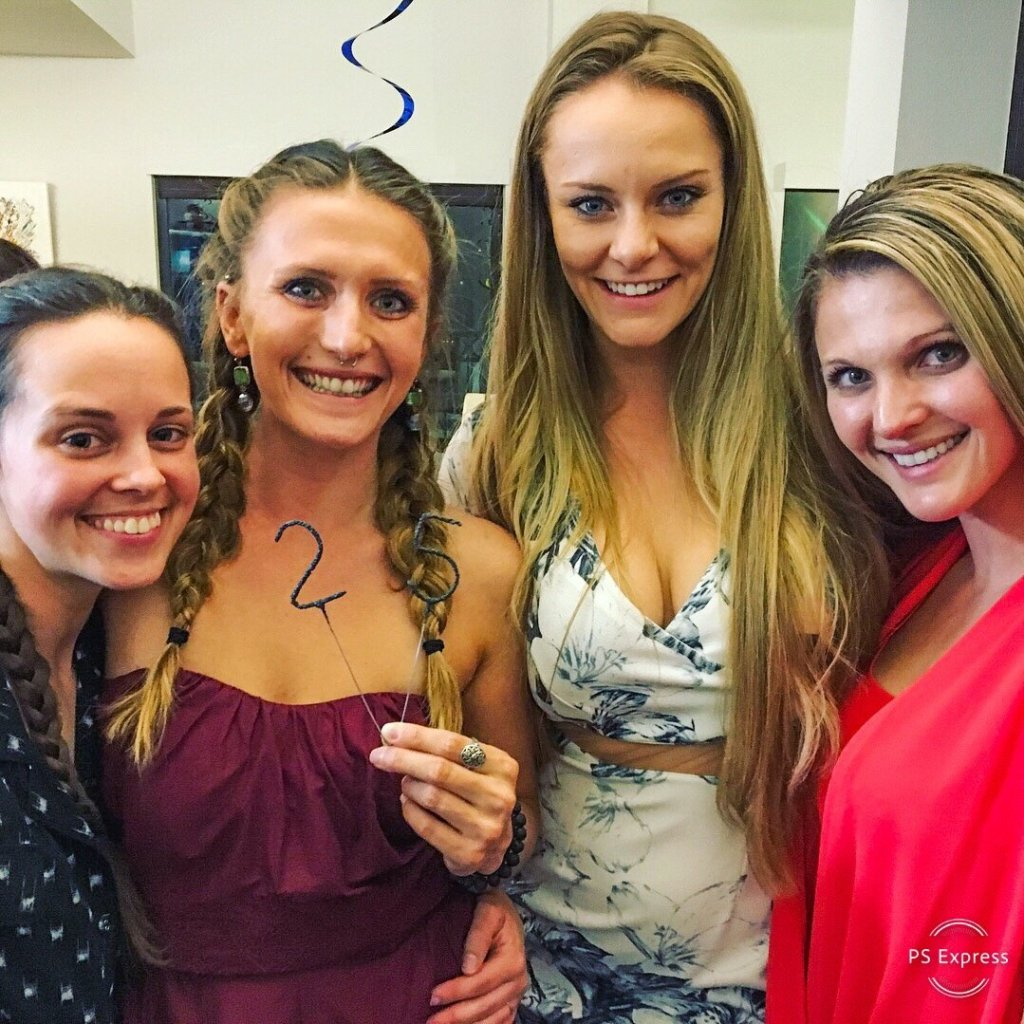 four-women-smiling-one-holding-25-candles